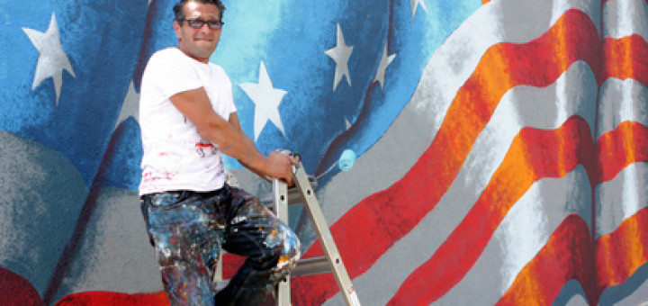 Artist Scott LoBaido just finished painting the american flag on the side of the store on Melvin Ave. & Victory Blvd. as the Travis 4th of July Parde is going on.